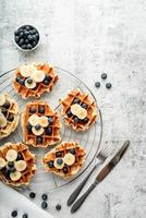 Top view of fresh made waffles with blueberries, banana and yoghurt photo