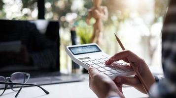 woman accountant or banker using calculator in retro office. photo