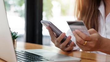 pago en línea manos de mujer sosteniendo smartphone foto