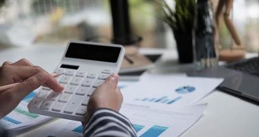 Cerrar el presupuesto de planificación de la mujer, con calculadora y portátil foto