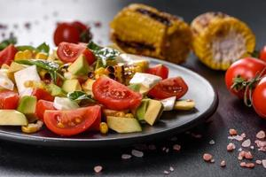Delicious fresh salad with tomatoes, avocado, cheese and grilled corn photo