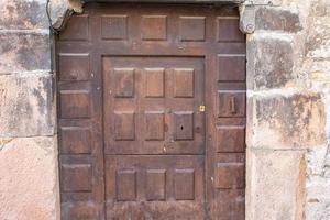 Puerta de madera antigua en fachada de piedra foto