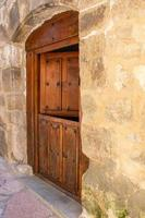 Puerta doble de madera antigua en fachada de piedra foto