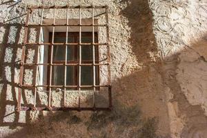 Ventana antigua con barandillas en fachada de piedra foto