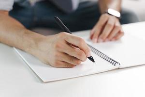 Cerca de las manos del hombre escribiendo en el bloc de notas, cuaderno. foto