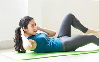 Young asian girl doing exercise on the floor alone photo