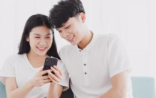Young couple looking at the phone together with happy expression photo