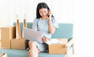 joven asiática sentada en casa vendiendo en línea foto