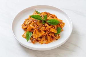 Farfalle pasta with basil and garlic in tomato sauce - Italian sauce photo