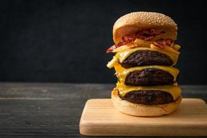 Hamburger or beef burgers with cheese, bacon, and french fries - unhealthy food style photo