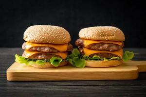 Pork hamburger or pork burger with cheese on wooden board photo