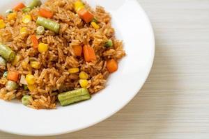 arroz frito con guisantes, zanahoria y maíz - estilo de comida vegetariana y saludable foto