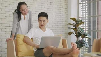 Asian family couple husband and wife work and using laptop computer analyzing finances discuss. Cheerful loving couple smile shopping order products online together from home by computer, slow motion video