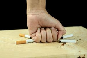 Woman's fist crushing cigarettes on black background photo