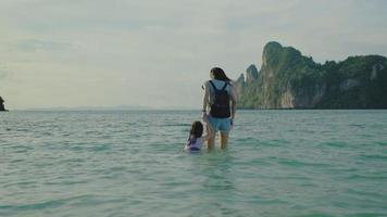 Mother lovingly holding hand with her young daughter on outdoor beach. video