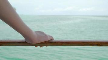 Woman's hand holding wooden railing of the sea raft. video
