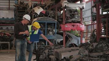 deux ouvriers masculins vérifiant les pièces du moteur dans un entrepôt. video