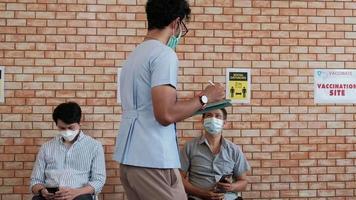 La enfermera revisa la cola de vacunación contra el coronavirus. video