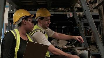 deux ingénieurs d'usine parlant sur le chariot élévateur. video