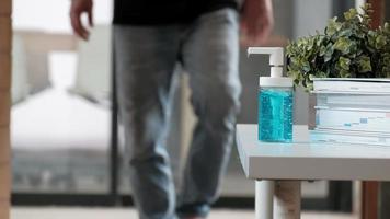 un homme décontracté appuie sur une bouteille de gel alcoolisé et nettoie les mains. video