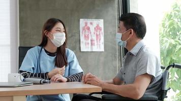 sênior com deficiência em cadeira de rodas, consultando uma médica asiática. video