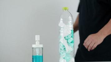 homem está descartando a máscara usada em um frasco vazio e limpando as mãos com álcool gel para higiene, a fim de evitar a propagação de doenças, infecção pelo coronavírus covid-19 e bactérias. video