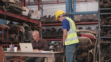zwei Männer im Lager für Kfz-Ersatzteile. Der kaukasische Besitzer verwendet Laptops, um Bestellungen zu überprüfen, und macht einen asiatischen männlichen Mitarbeiter für die Fehler von Industriemotorenteilen in einer Fabrik verantwortlich. video