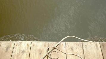 perto de pranchas de assoalho de madeira velhas e cordas de jangada de bambu, movendo-se em um rio turbulento, amarelo calmo. é o plano de fundo pacífico do espaço da cópia da natureza tropical ao ar livre nas longas férias. video