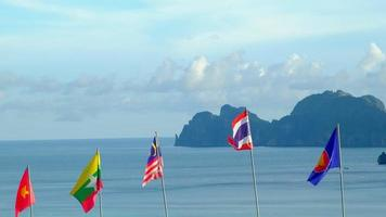 The blowing flags of ASEAN community - Thailand, Malaysia, Vietnam, and  Union of Myanmar -Fluttering freely in sea background, mountains, and blue sky. And beautiful scenery of the island. video