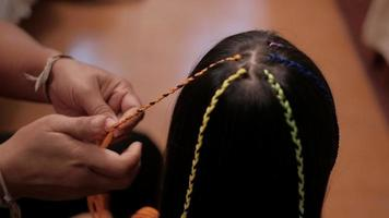 Close-up VDO. Cute long, black hair Asian girl is being braided in multi-colored threads by woman's hand in beauty salon. Child-like fashion, weaving pigtails with decoration yarn or knitting wool. video