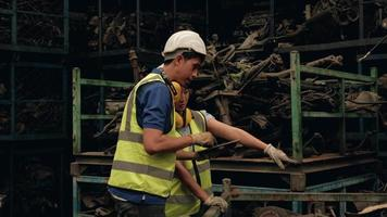 travailleurs asiatiques masculins et féminins en uniformes et casques, vérification des stocks des employés de l'usine d'entrepôt de pièces détachées automobiles. à l'aide d'une tablette pour vérifier les anciens moteurs et les commandes de machines pour l'industrie automobile. video