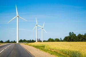 molinos de viento a lo largo de la carretera contra el cielo azul foto