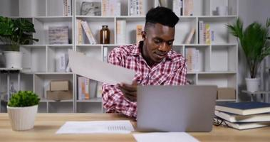 Young man busy during work with documents on table video