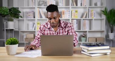 junger Mann, der von zu Hause aus am Laptop arbeitet video