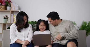 jeune père et mère apprenant à sa fille à utiliser un ordinateur video