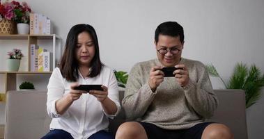 pareja feliz usando un teléfono inteligente jugar al juego móvil video