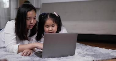 mère enseignant petite fille utiliser un ordinateur portable video