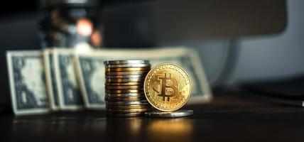 gold bitcoins placed on a wooden desk photo