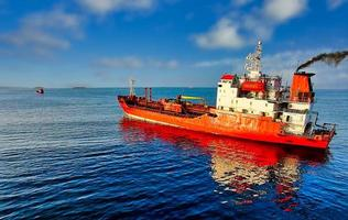 Seascape with a red ship on a blue sea background photo