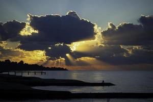 Seascape with a bright sunset and rays through the clouds photo