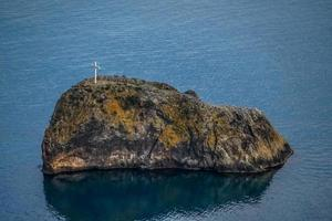 A small island in the sea with stairs photo