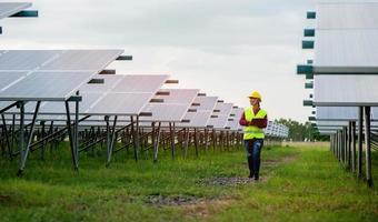 Ingeniero de sexo femenino asiático caminar inspeccionar el equipo en una energía solar foto