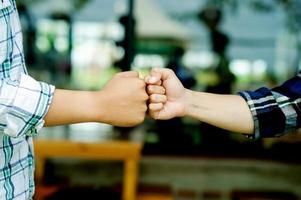 Unidad de trabajo en equipo de dos puños cerca de dos manos mostrando foto