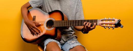 El guitarrista masculino está afinando su guitarra antes de tocar la guitarra cada vez. foto