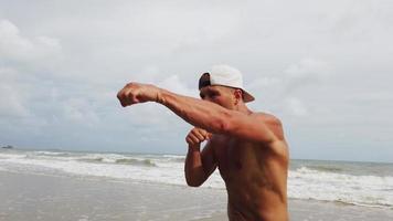 homem fazendo exercício matinal na praia com boxe video