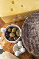 assorted cheeses platter with seasoned olives photo