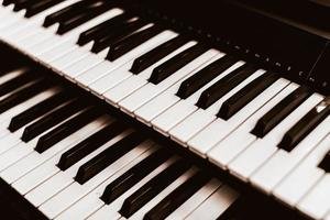 Close focus on upper row of piano with warm tone of black and white. photo