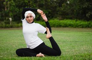 Pleasant woman in hijab and sportswear doing yoga and stretching. photo