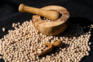 a pile of chick peas and a wooden spoon photo