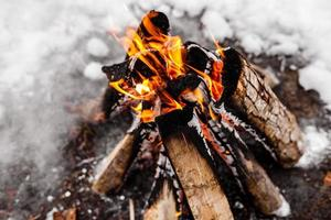 Campfire burns in the snow in the woods. campfire burning photo